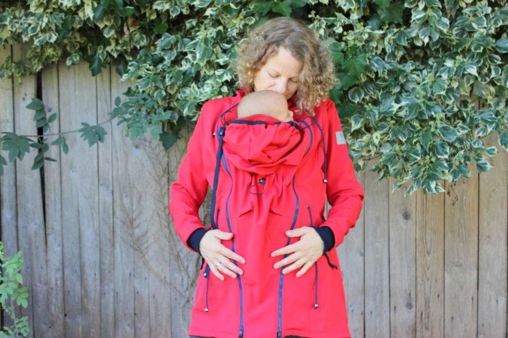 Mutter gibt Baby in roter Tragejacke einen Kuss auf den Kopf